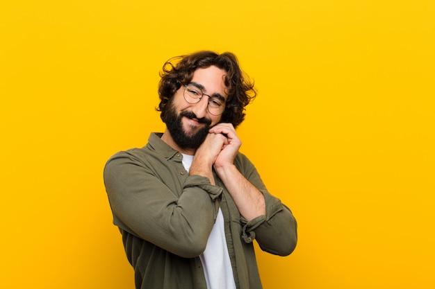 Jovem homem louco se sentindo apaixonado e bonito, adorável e feliz, sorrindo romanticamente com as mãos ao lado de enfrentar a parede amarela