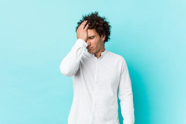 Jovem homem maduro encaracolado vestindo uma camisa elegante, esquecendo de algo, batendo na testa com a palma da mão e fechando os olhos.