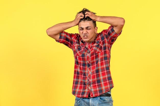 Jovem homem muito zangado de frente para uma camisa brilhante em fundo amarelo