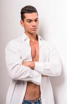 Jovem homem musculoso com torso perfeito na camisa aberta.