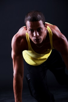 Jovem homem musculoso está pronto para correr