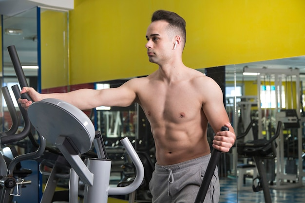 Jovem homem musculoso exercitando-se na máquina elíptica, dentro de um ginásio.