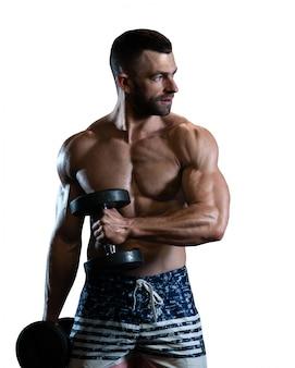 Jovem homem musculoso exercitar com halteres. cara treina seu bíceps