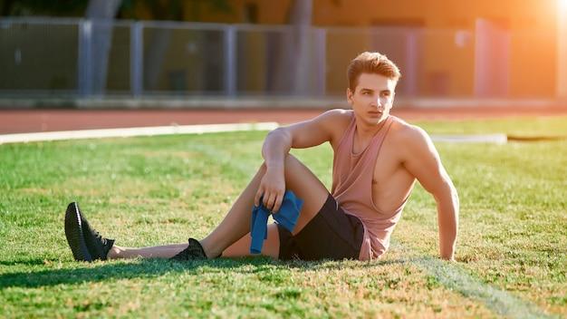Jovem homem musculoso exercitar-se com resistência elástico no estádio