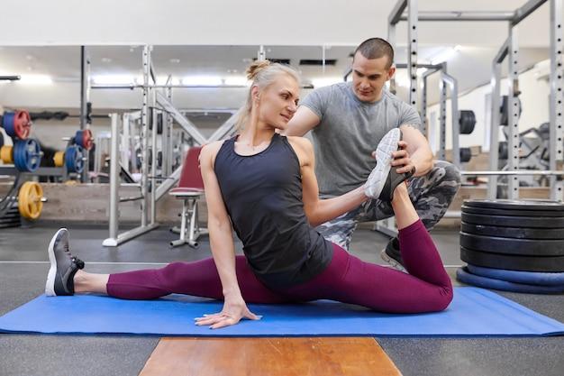 Jovem homem musculoso forte ajudando jovem mulher atlética alongamento