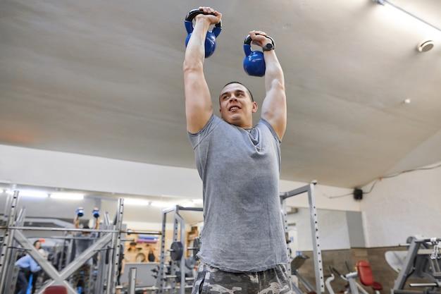 Jovem homem musculoso forte no ginásio, levantamento de pesos pesados