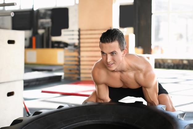 Jovem homem musculoso jogando pneu pesado na academia