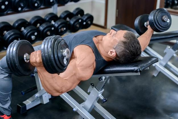 Jovem homem musculoso malhando na academia