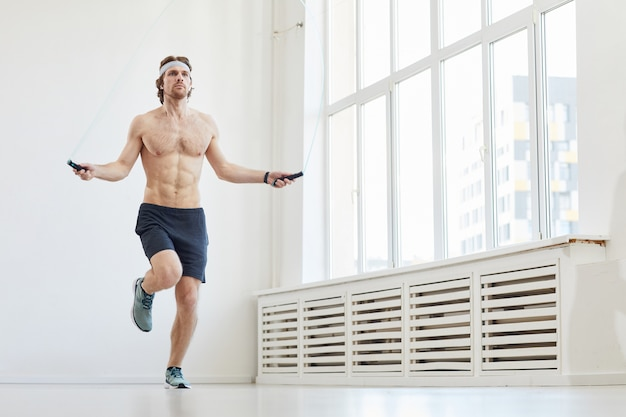 Jovem homem musculoso pulando na corda de pular durante o treinamento esportivo