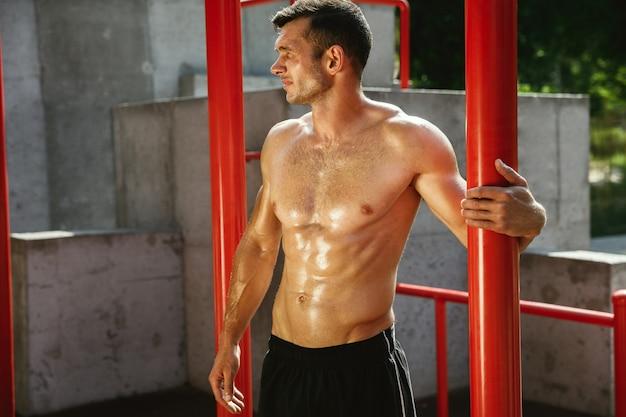 Jovem homem musculoso sem camisa, caucasiano, enquanto se exercita nas barras horizontais do playground em um dia ensolarado de verão