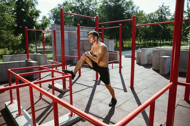 Jovem homem musculoso sem camisa, caucasiano, fazendo exercícios de alongamento