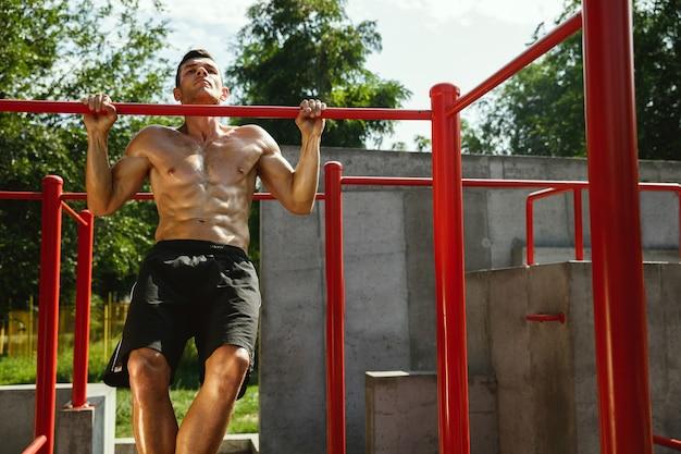 Jovem homem musculoso sem camisa, caucasiano, pulando acima da barra horizontal
