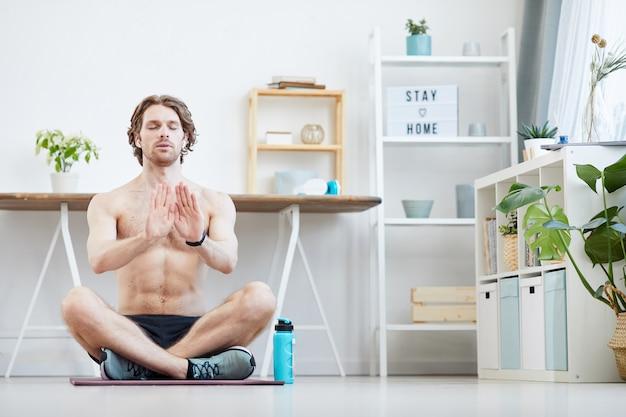 Jovem homem musculoso sentado na esteira de exercícios com os olhos fechados e fazendo exercícios respiratórios em casa