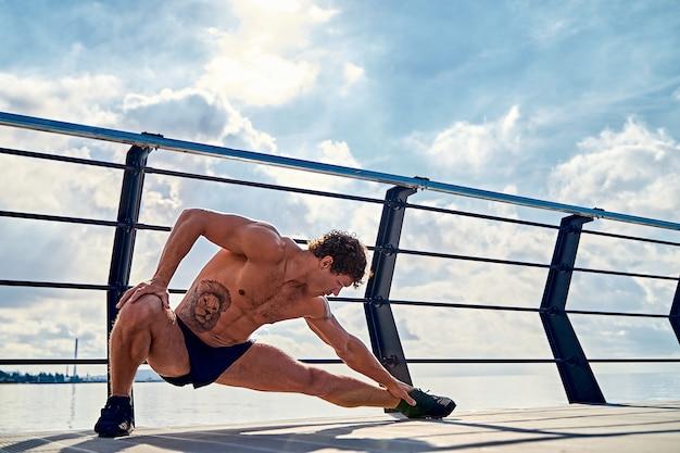 Jovem homem musculoso tatuado fazendo exercícios de alongamento no início da manhã no cais à beira-mar