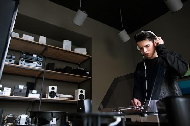 Jovem homem na loja de música. compra de discos de vinil. ouvir áudio em fones de ouvido, estilo de vida moderno
