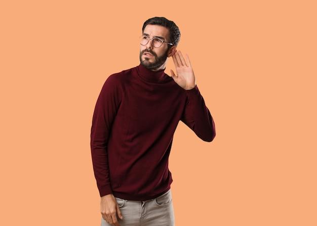 Jovem homem natural tenta ouvir uma fofoca