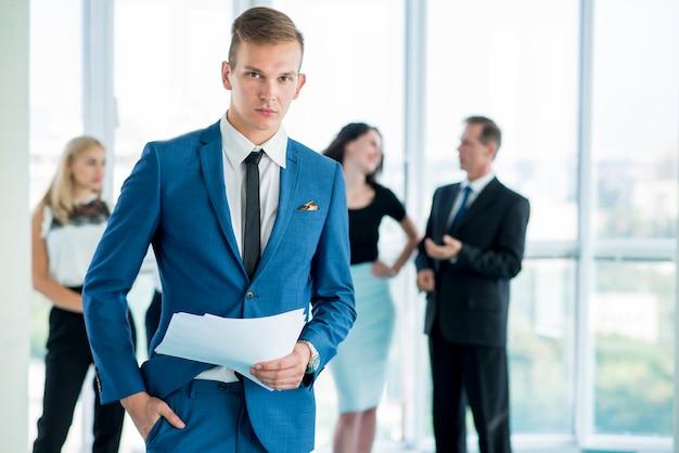 Jovem, homem negócios, com, documentos, ficar, em, escritório