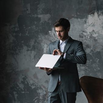Jovem, homem negócios fica, contra, um, antigas, parede, abertura, a, laptop