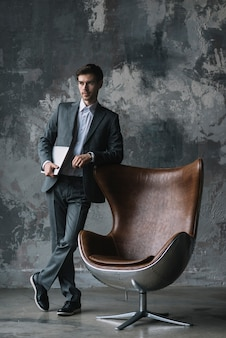 Jovem, homem negócios fica, frente, parede resistida, inclinar-se, modernos, cadeira, segurando, laptop, em, mão