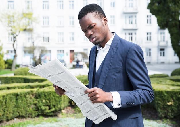 Jovem, homem negócios, lendo jornal