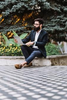 Jovem, homem negócios, sentando, ao ar livre, usando, laptop