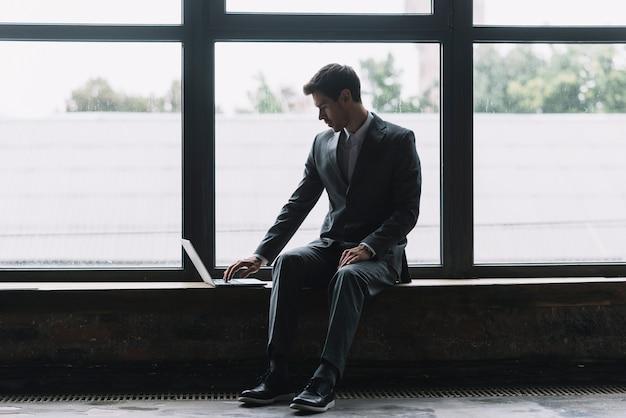 Jovem, homem negócios, sentando, frente, janela, digitando, ligado, laptop