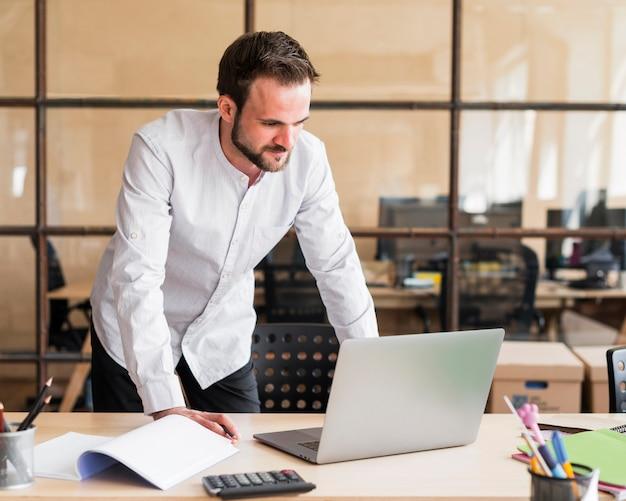 Jovem, homem negócios, trabalhando, com, laptop, em, escritório
