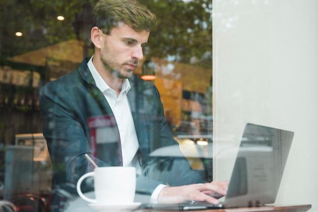 Jovem, homem negócios, usando computador portátil, com, xícara café, em, café