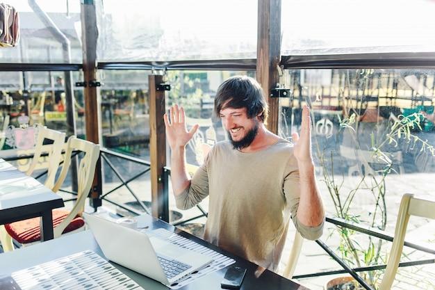 Jovem, homem negócios, usando computador portátil, em, café