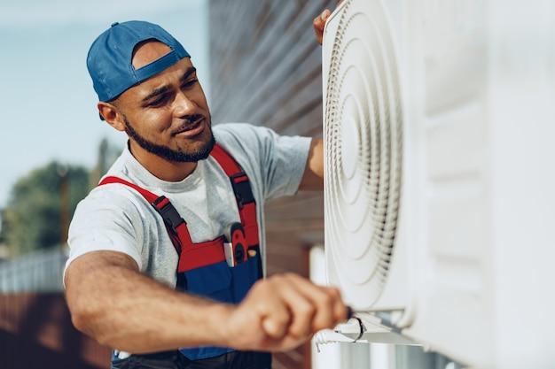 Jovem homem negro reparador verificando uma unidade externa de ar condicionado