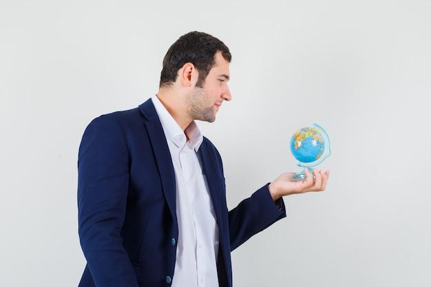 Jovem homem olhando para o globo da escola com camisa e jaqueta e parecendo pensativo