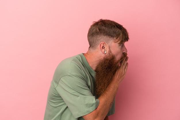 Jovem homem ruivo, caucasiano, com barba comprida, isolado em um fundo rosa, está contando uma notícia secreta de travagem e olhando para o lado