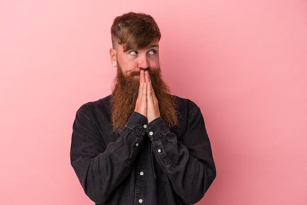 Jovem homem ruivo, caucasiano, com barba comprida, isolado em um fundo rosa orando, mostrando devoção, pessoa religiosa em busca de inspiração divina.