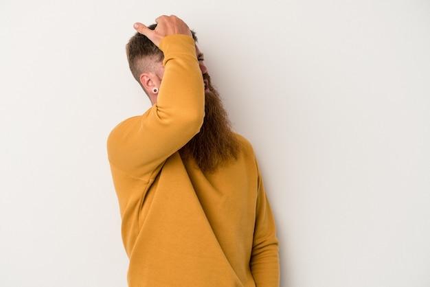 Jovem homem ruivo, caucasiano, com barba comprida, isolado no fundo branco, esquecendo de algo, batendo na testa com a palma da mão e fechando os olhos.