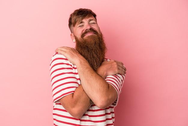 Jovem homem ruivo, caucasiano, com barba comprida, isolado no fundo rosa abraços, sorrindo despreocupado e feliz.