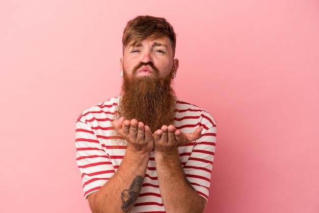 Jovem homem ruivo, caucasiano, com barba comprida, isolado no fundo rosa, dobrando os lábios e segurando as palmas das mãos para enviar beijo no ar.