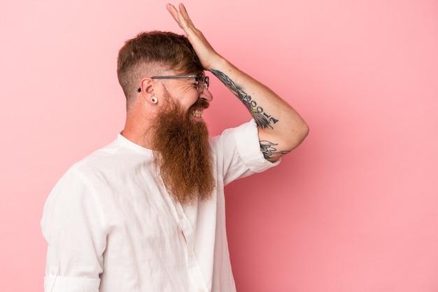 Jovem homem ruivo, caucasiano, com barba comprida, isolado no fundo rosa, esquecendo de algo, batendo na testa com a palma da mão e fechando os olhos.