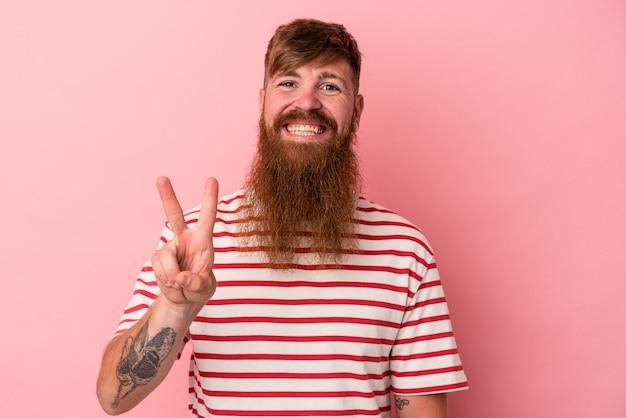 Jovem homem ruivo, caucasiano, com barba comprida, isolado no fundo rosa, mostrando sinal de vitória e sorrindo amplamente.