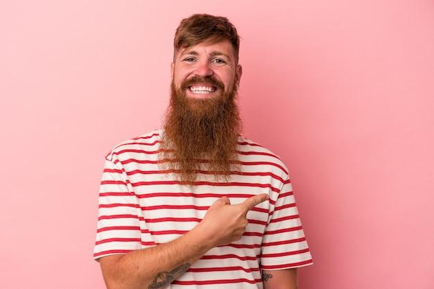 Jovem homem ruivo, caucasiano, com barba comprida, isolado no fundo rosa, sorrindo e apontando de lado, mostrando algo no espaço em branco.