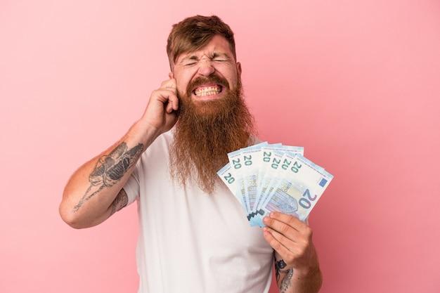 Jovem homem ruivo, caucasiano, com barba comprida, segurando notas isoladas no fundo rosa, cobrindo as orelhas com as mãos.