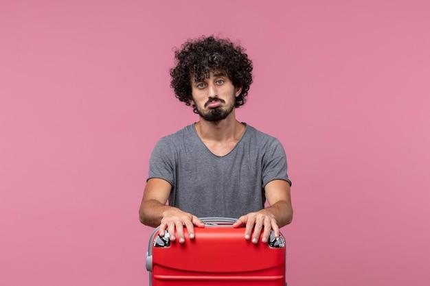 Jovem homem se preparando para a viagem com a bolsa na mesa rosa