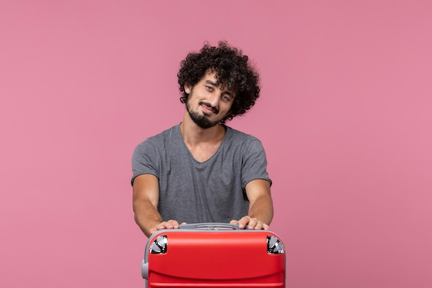 Jovem homem se preparando para as férias com sua bolsa vermelha no espaço rosa