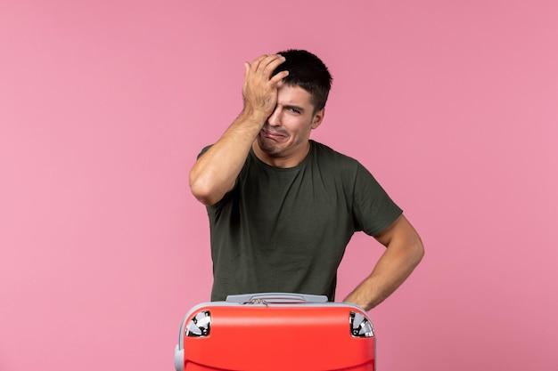 Jovem homem se preparando para as férias e chorando na mesa rosa