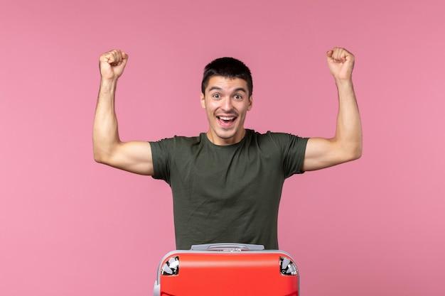 Jovem homem se preparando para as férias e se sentindo feliz no espaço rosa