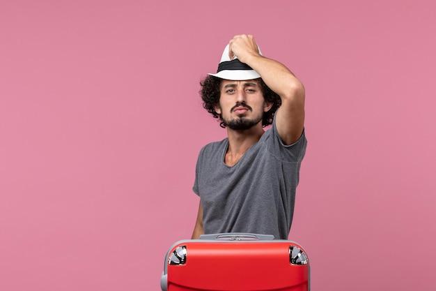 Jovem homem se preparando para as férias segurando um chapéu no espaço rosa