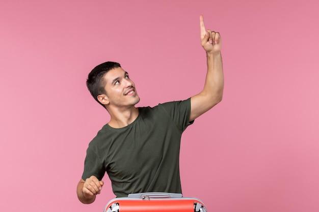 Jovem homem se preparando para as férias sorrindo no espaço rosa