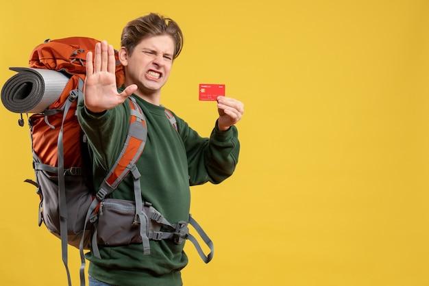 Jovem homem se preparando para uma caminhada segurando um cartão de banco vermelho