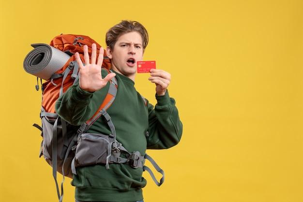 Jovem homem se preparando para uma caminhada segurando um cartão de banco
