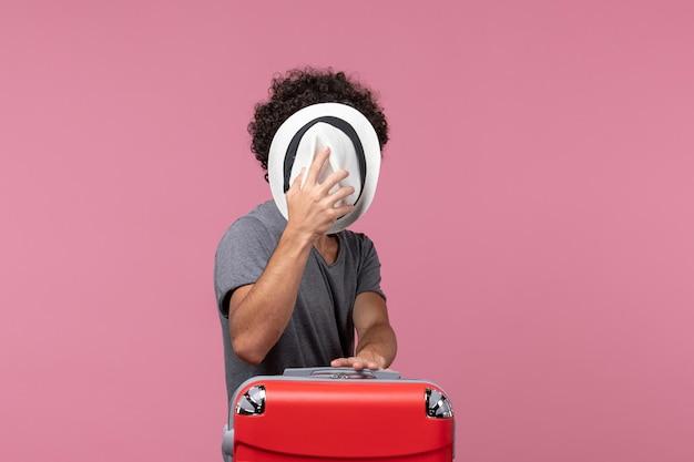 Jovem homem se preparando para uma viagem e segurando um chapéu na mesa rosa