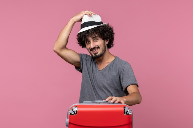 Jovem homem se preparando para uma viagem e segurando um chapéu no espaço rosa